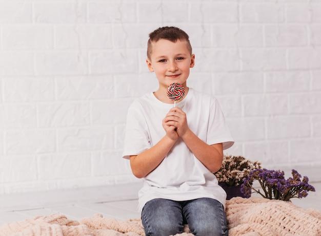 Ładny chłopak z okrągłymi lizakami w dłoniach na białej powierzchni
