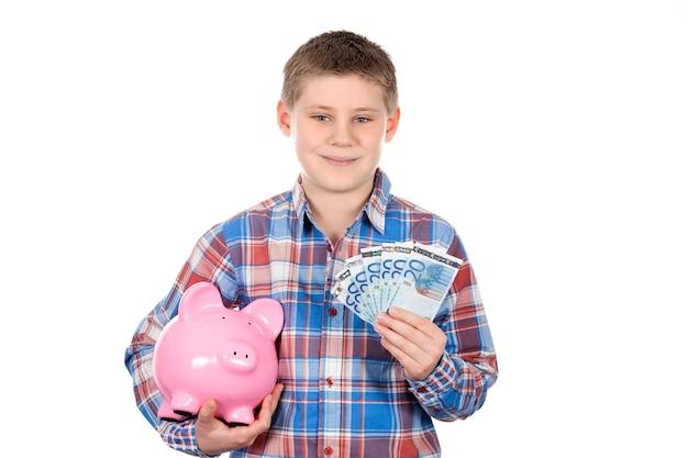 Ładny chłopak z piggy bank i banknot na białej przestrzeni