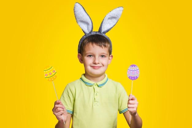 Ładny chłopak z uszami królika trzyma w rękach kolorowe jajka na żółtym tle