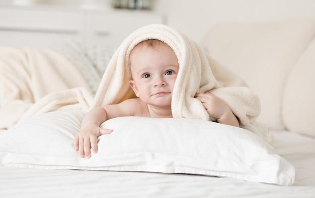 Ładny chłopczyk leżący na łóżku pod ręcznikiem po kąpieli