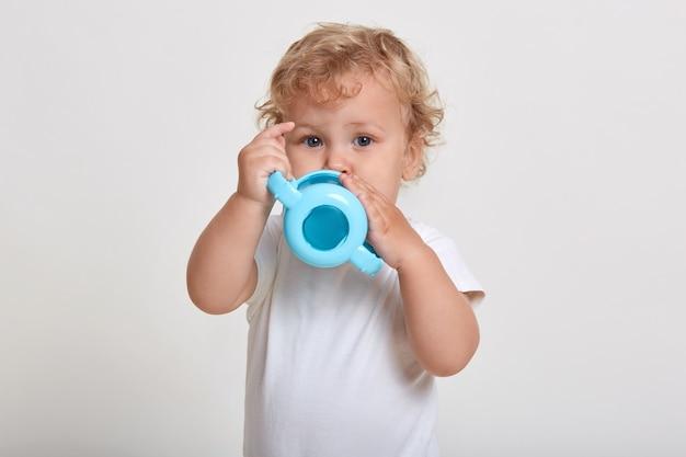 Ładny chłopczyk pije z butelki, dziecko płci męskiej na sobie t shirt, ma blond falowane włosy