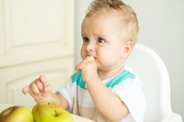 Ładny chłopczyk siedzi przy stole w foteliku dla dziecka je jabłko w białej kuchni