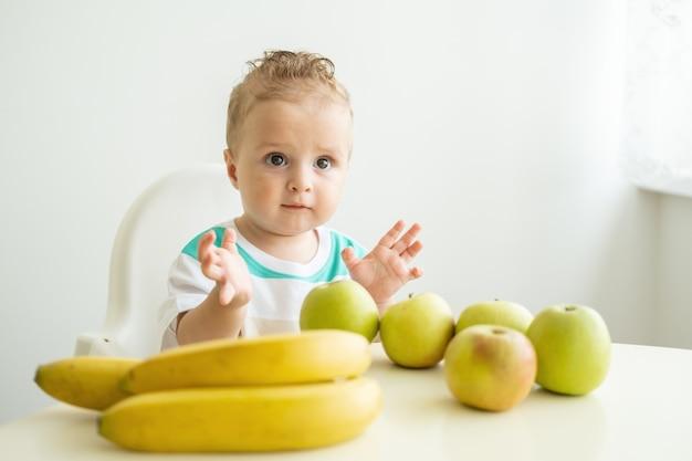 Ładny chłopczyk siedzi przy stole w fotelu dla dziecka je jabłko w białej kuchni
