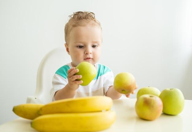 Ładny chłopczyk siedzi przy stole w fotelu dziecko jedzenie jabłko na białej kuchni.