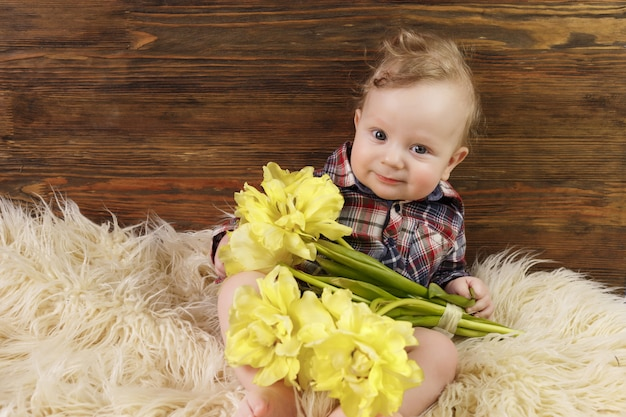 Ładny chłopczyk siedzi z żółtymi tulipanami w ręku