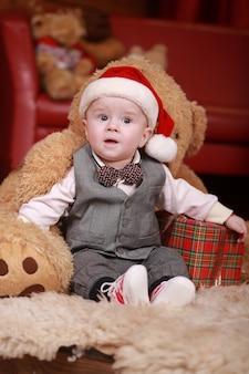 Ładny chłopczyk w czapce mikołaja z wielkim misiem i prezentami świątecznymi.