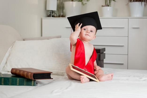 Ładny chłopczyk w tablicy do zaprawy murarskiej akademicki siedzący na łóżku