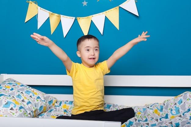 Ładny chłopczyk z zespołem downa na łóżku w sypialni w domu