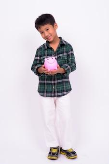 Ładny chłopiec azjatyckich sobie zieloną koszulę w kratkę na białej ścianie
