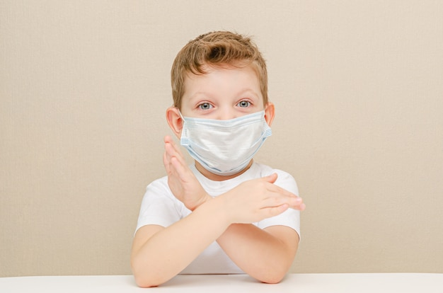 Ładny chłopiec czterech lat w masce medycznej. dzieci poddane kwarantannie z powodu epidemii. chłopiec zabrania. gest - ręce są skrenne.