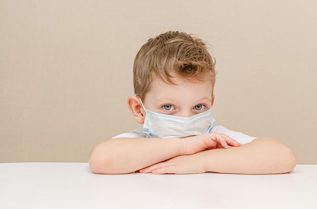 Ładny chłopiec czterech lat w masce medycznej. dzieci poddane kwarantannie z powodu epidemii.