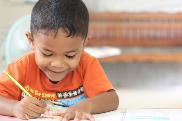 Ładny chłopiec dziecko studia i myślenia w domu.