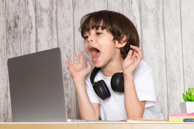 Ładny chłopiec dziecko w białych t-shirtowych czarnych słuchawkach za pomocą szarego laptopa na stole wraz z zieloną rośliną