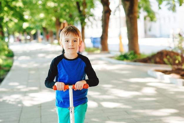 Ładny chłopiec na skuterze jeżdżącym w letnim parku zdrowy styl życia i sport rekreacyjny
