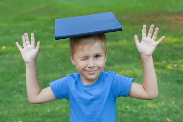 Ładny chłopiec siedzi na trawie w parku i trzyma książkę na głowie, mrugając okiem.