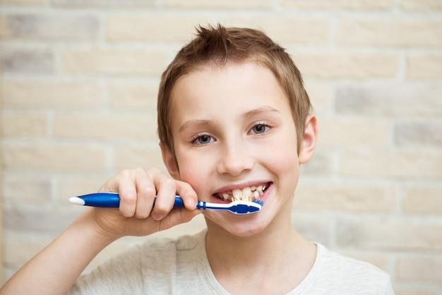 Ładny chłopiec szczotkuje zęby. jasne tło