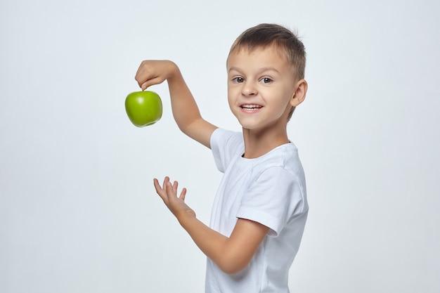 Ładny chłopiec trzyma zielone jabłko.