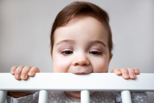 Ładny ciekawy dziecko stojąc w białym łóżeczku.