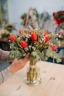 Ładny czerwony i pomarańczowy tulipanowy bukiet na drewnianym stole
