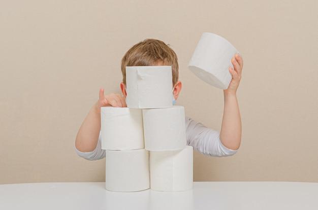 Ładny czteroosobowy chłopiec w ochronnej masce medycznej bawi się papierem toaletowym
