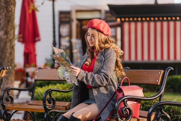 Ładny długowłosy kobieta z kręconymi fryzurami patrząc na mapę miasta z zainteresowaniem