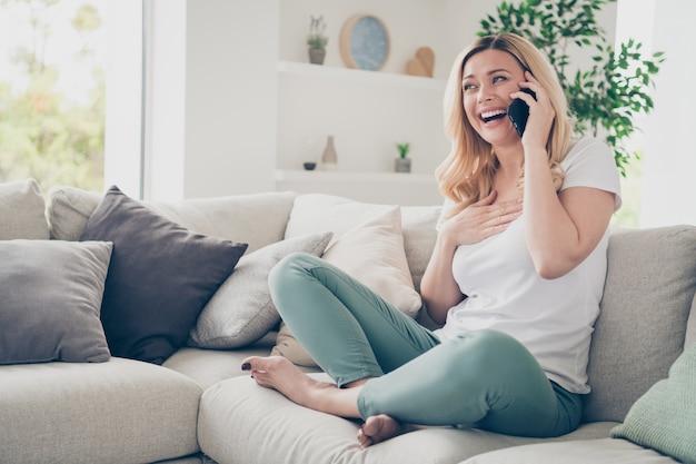 Ładny domowy wesoły piękna dama siedzieć na kanapie trzymać telefon rozmawiając