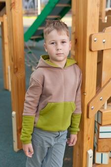 Ładny dziarski chłopiec przedszkolak zabawy na placu zabaw na świeżym powietrzu. wiosną, latem lub jesienią aktywny wypoczynek sportowy dla dzieci. zajęcia na świeżym powietrzu dla rodziny z dziećmi
