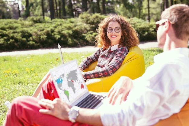 Ładny dzień. wesoła dziewczyna z kręconymi włosami pracuje na swoim laptopie i jej kolega student siedzi