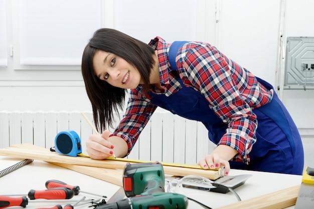 Ładny dziewczyna budowniczy mierzy deskę drewno
