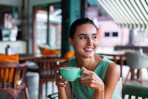Ładny elegancki spokojny szczęśliwy kobieta w zielonej letniej sukience siedzi z kawą w kawiarni ciesząc się rano