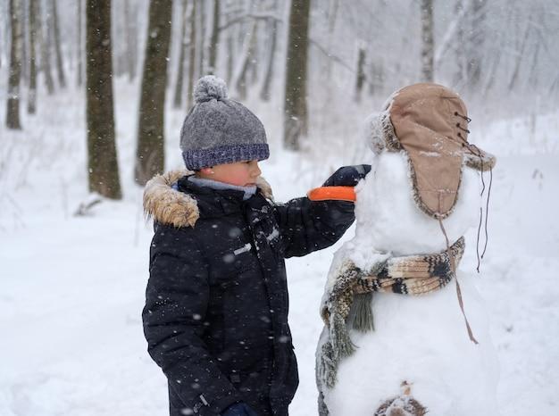 Ładny europejski chłopiec i zabawny bałwan w zaśnieżonym lesie w zimowy dzień w śniegu