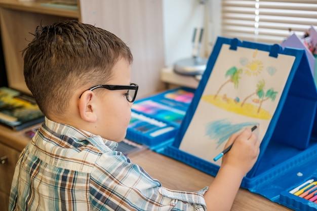 Ładny europejski chłopiec w okularach rysuje na papierze ołówkami, siedząc przy stole. proces tworzenia rysunku dla dzieci