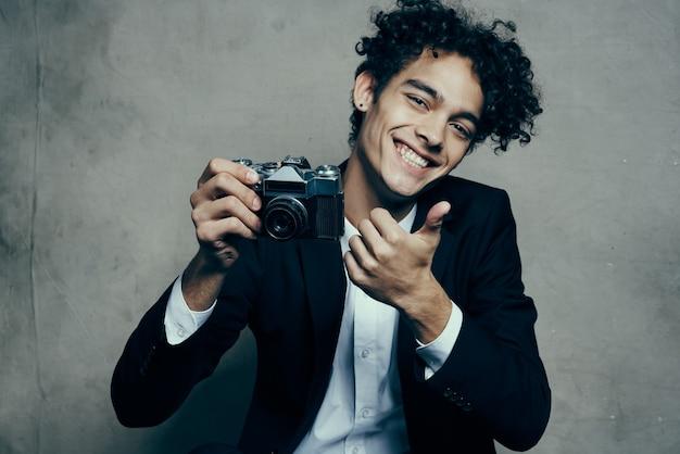 Ładny facet trzymając aparat klasyczny garnitur, gestykulując rękami uśmiech radość modelu