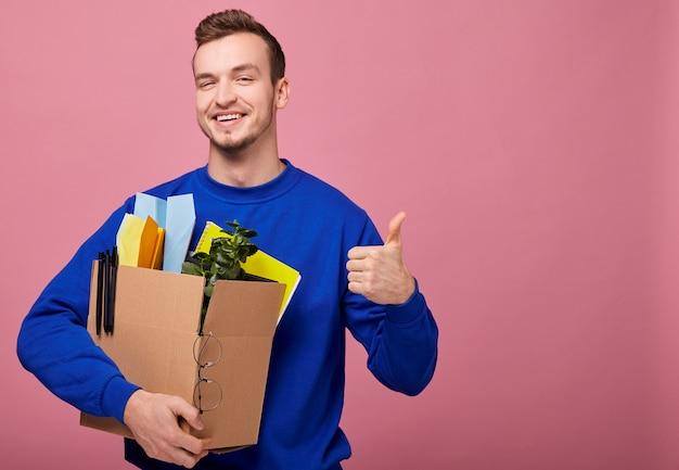 Ładny facet tuli pudełko z zieloną rośliną, żółtym notatnikiem i papierowym samolotem i pokazuje jak
