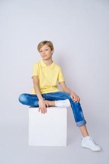 Ładny facet w żółtej koszulce i niebieskich dżinsach na białym tle siedzi na sześcianie i pozuje