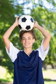 Ładny gracz futbolu ono uśmiecha się przy kamerą