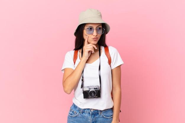 Ładny hiszpański turysta uśmiechający się ze szczęśliwym, pewnym siebie wyrazem twarzy z ręką na brodzie z aparatem fotograficznym i kapeluszem
