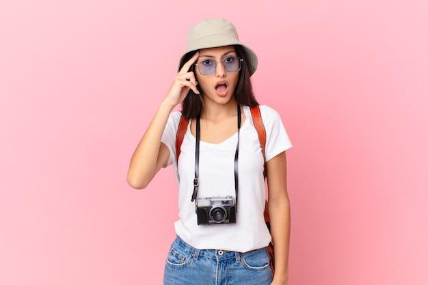 Ładny hiszpański turysta wyglądający na zaskoczonego, realizujący nową myśl, pomysł lub koncepcję z aparatem fotograficznym i kapeluszem