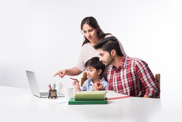 Ładny indyjski chłopiec z ojcem i matką studiuje lub odrabia pracę domową w domu za pomocą laptopa i książek - koncepcja edukacji onlineing