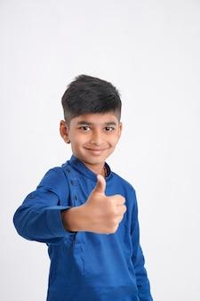 Ładny indyjski mały chłopiec pokazując wali