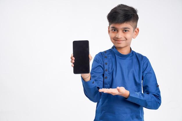 Ładny indyjski mały chłopiec pokazuje ekran inteligentnego telefonu na białym tle