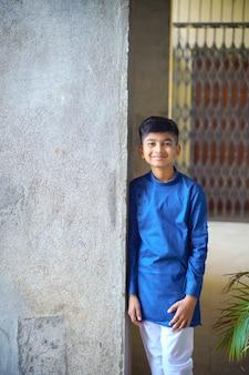 Ładny indyjski mały chłopiec w etniczne zużycie i pokazując wypowiedzi na białym tle