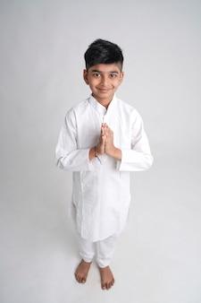 Ładny indyjski mały chłopiec w namaste lub modląc się poza na białym tle
