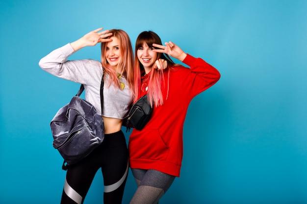 Ładny jasny portret dwóch szczęśliwych ładnych hipster dziewcząt ubranych w sportowe ubrania na fitness i plecak, uśmiechnięta i przytula, niebieska ściana.