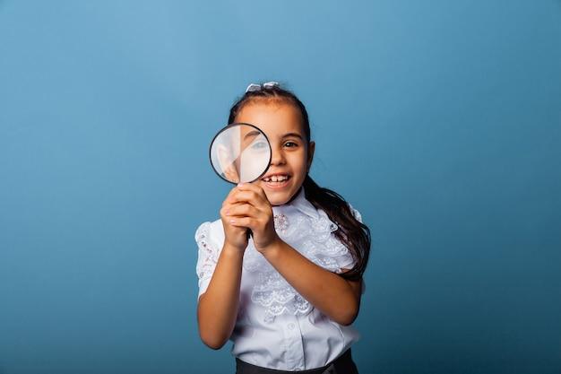 Ładny kaukaski dziewczynka bawi się lupą na niebieskim tle.