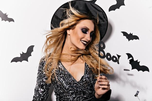 Ładny kaukaski kobieta w kapeluszu kreatora. wspaniała blondynka w stroju czarownicy uśmiechnięta w halloween.