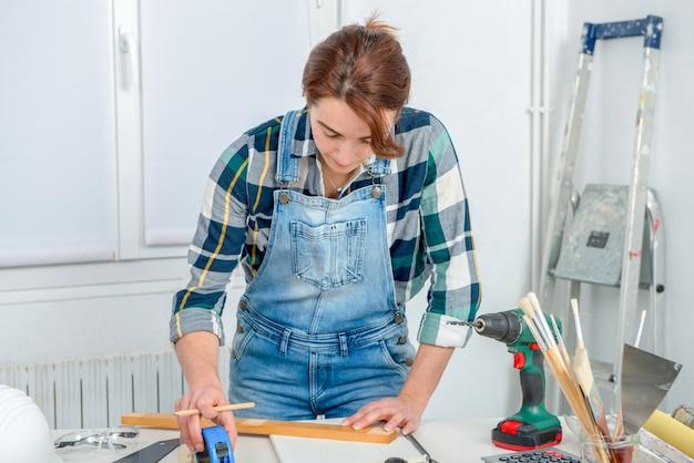 Ładny kobieta budowniczy mierzy deskę drewno