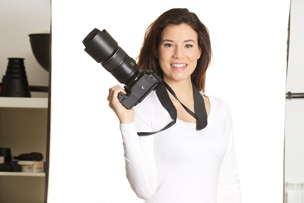 Ładny kobieta fotograf pracuje w studiu