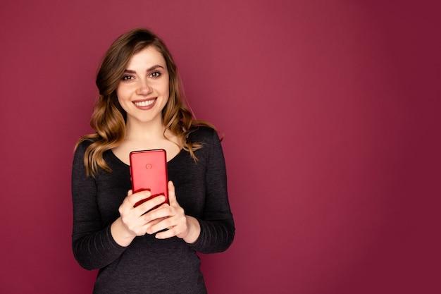 Ładny kobieta trzymając telefon komórkowy i uśmiechnięty na białym tle nad różowym tle.