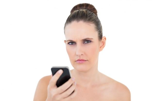 Ładny kobiety mienia telefon patrzeje gniewny przy kamerą